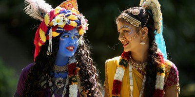 WATFORD, ENGLAND - AUGUST 28:  Laxmipriya Patel (L), aged 20, dressed as the Hindu god Lord Krishna, and her sister Mohini Patel, aged 13, dressed as Lord Krishna's devotee Radharani, walk through the George Harrison Memorial Garden during the Janmashtami Hindu Festival at Bhaktivedanta Manor on August 28, 2013 in Watford, England. Up to 72,000 were expected to take part in the Hindu festival of 'Janmashtami', which falls on August 28 this year, and marks the birth of the Hindu god Lord Krishna. The festival is believed to be the largest Hindu festival gathering outside of India. Bhaktivedanta Manor is also celebrating it's 40th year since the manor house was donated to the Society of Krishna Consciousness by George Harrison in 1973.  (Photo by Christopher Furlong/Getty Images)